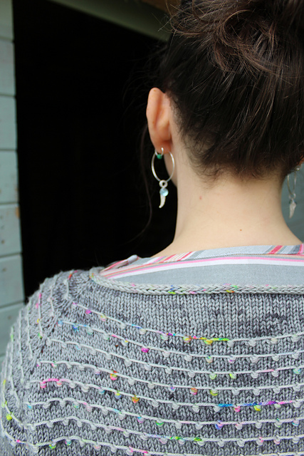 A woman's shoulders and head seen from behind wearing a sweater with a colourful yoke