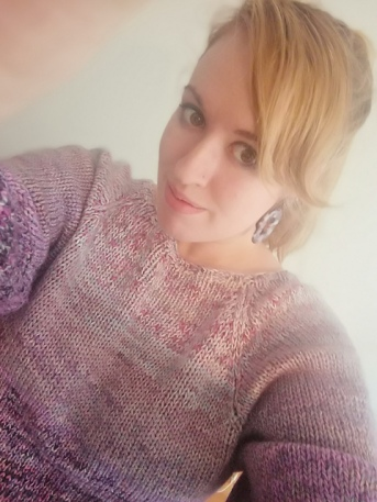 A selfie of a young woman wearing a lilac sweater