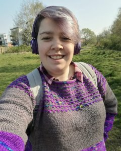 A white woman wearing a grey and purple colour block sweater and headphones standing in a field of grass, smiling