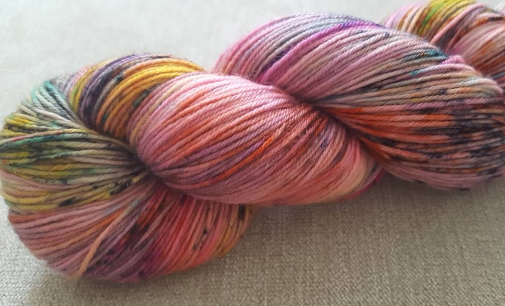 A skein of pastel pink 4ply yarn with rainbow speckles.